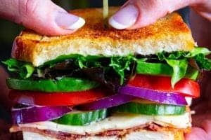 two hands holding a sandwich with lettuce, tomatoes, red onion, bacon, and sour dough bread