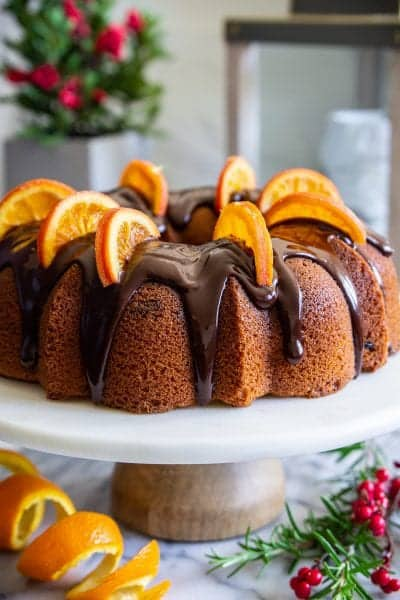 cranberry orange bundt cake with chocolate ganache on top, and dried orange slices on top, with an orange peal beside it