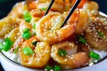 garlic ginger shrimp with green onion and sesame seeds on top in a white bowl with black chop sticks picking up the shrimp