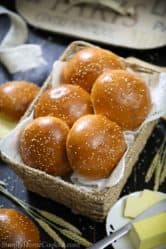 brioche buns in a basket with sliced butter beside it