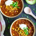 easy beef chili in 2 white bowls with sour cream, shredded cheddar, chopped green onion, and a sliced avocado on the side