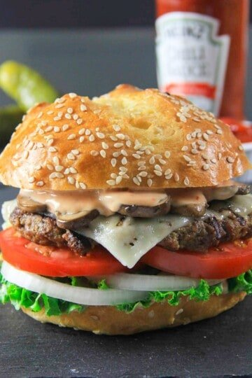 Beef burger with mushrooms, fry sauce, lettuce, tomatoes, onions, and brioche bun.