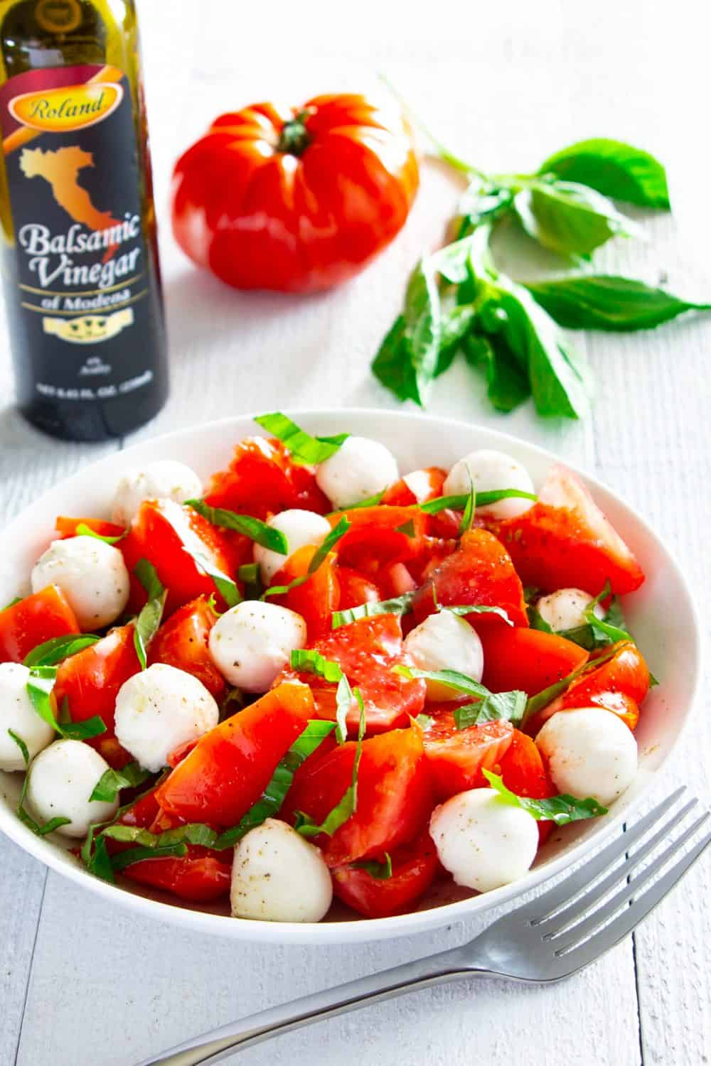 Chopped caprese salad in a bowl with tomato and a bottle of balsamic vinegar