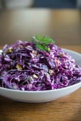 purple cabbage salad in a white plate with walnuts and dill on top