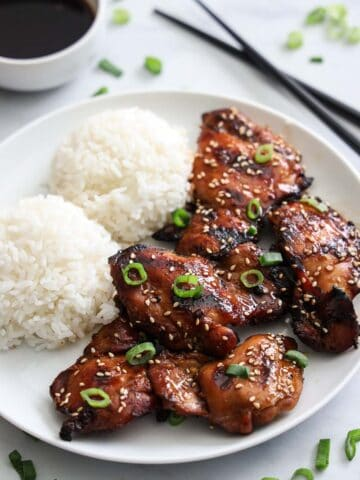 Plate of Grilled Teriyaki Chicken with rice and sauce nearby