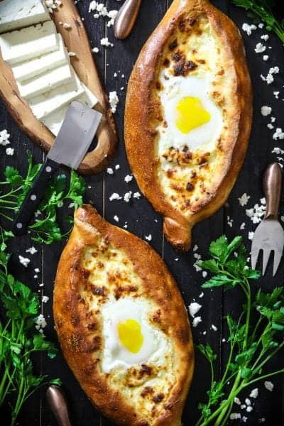 2 easy khachapuri breads with eggs in the center and sliced feta cheese and parsley beside it