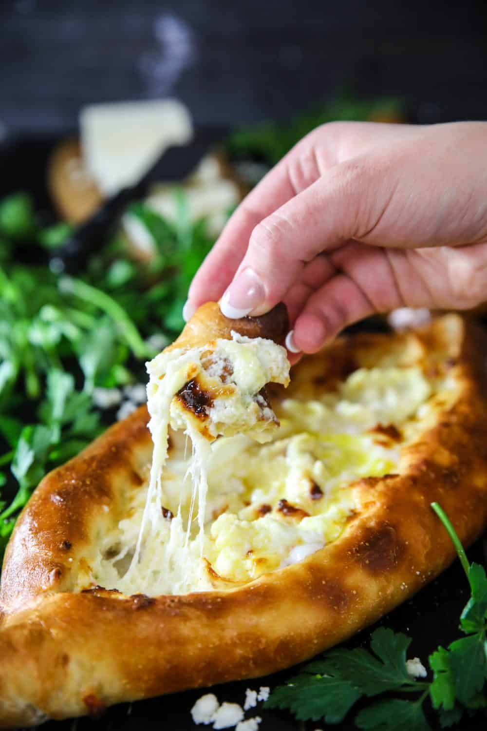 dipping bread into melted cheese from easy georgian khachapuri