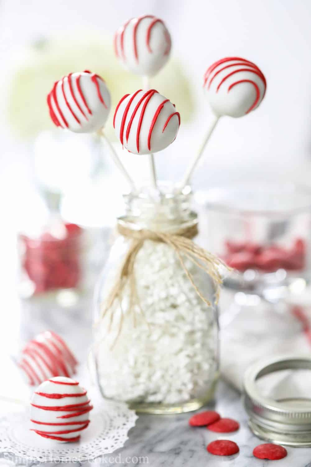red velvet cake pops in a glass bottle with burlap string around it.
