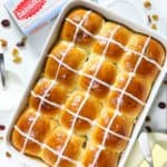 Warm fluffy and butter brioche hot cross buns in a white baking dish ready to eat