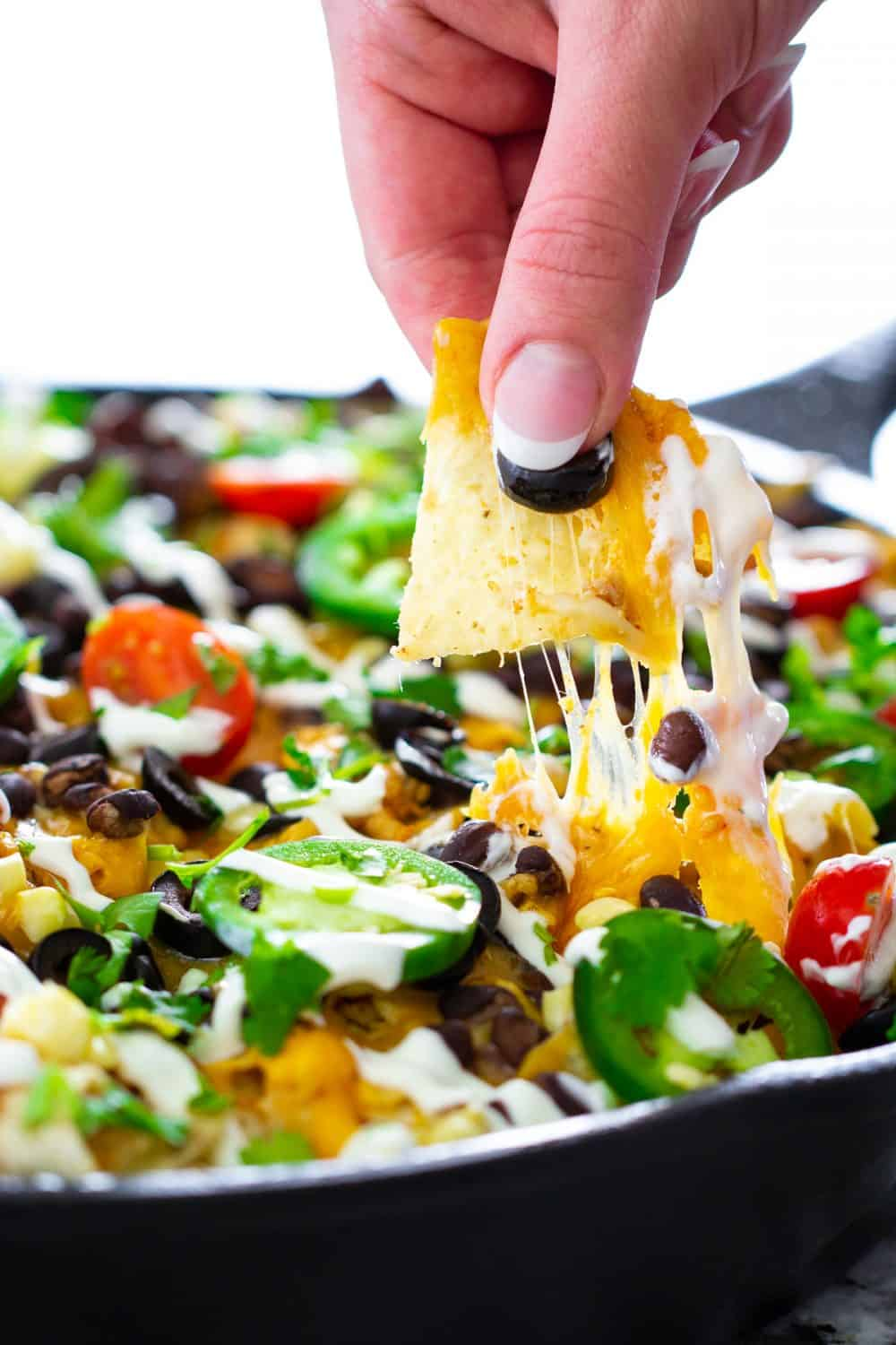 a close up shot of chicken nachos with a tortilla chip and cheddar cheese being pulled out of the skillet