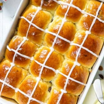 overhead image of fluffy brioche hot cross buns in a white baking dish with butter beside it