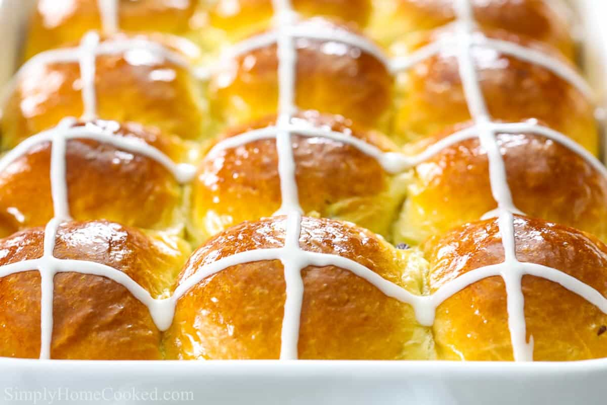 close up image of brioche hot cross buns in a white baking dish