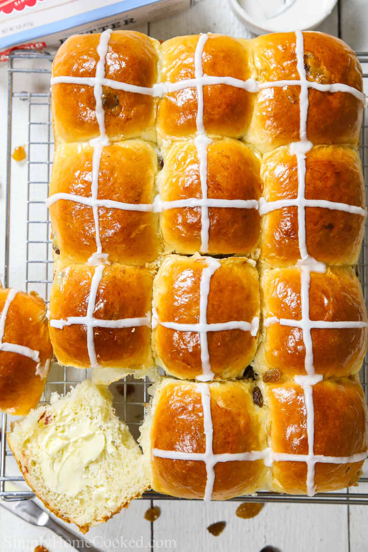 brioche hot cross buns cooling on a cooling rack and sliced open before they get smothered in salted butter
