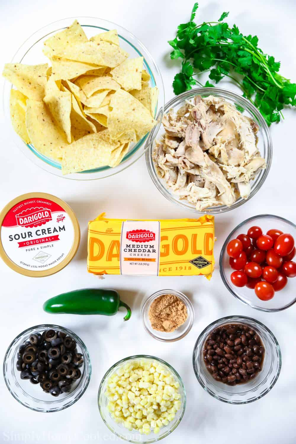 An overhead shot of ingredients for loaded chicken nachos including cheddar cheese, tortilla chips, shredded chicken, jalepeno, black beans, black olives, corn, cherry tomatoes. and cilantro