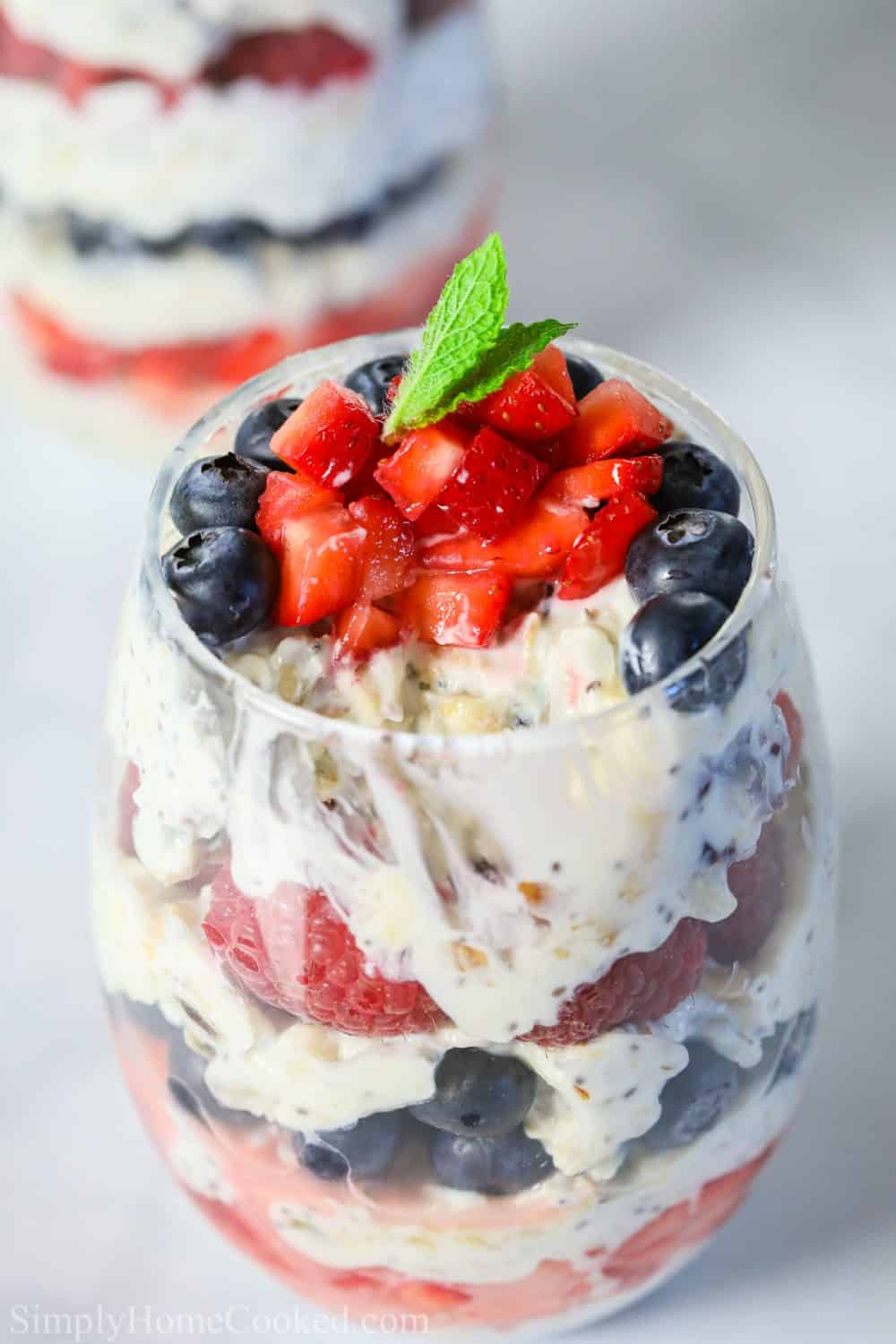 close up photo of yogurt berry parfait in a glass cup with chopped strawberries and a mint leaf on top