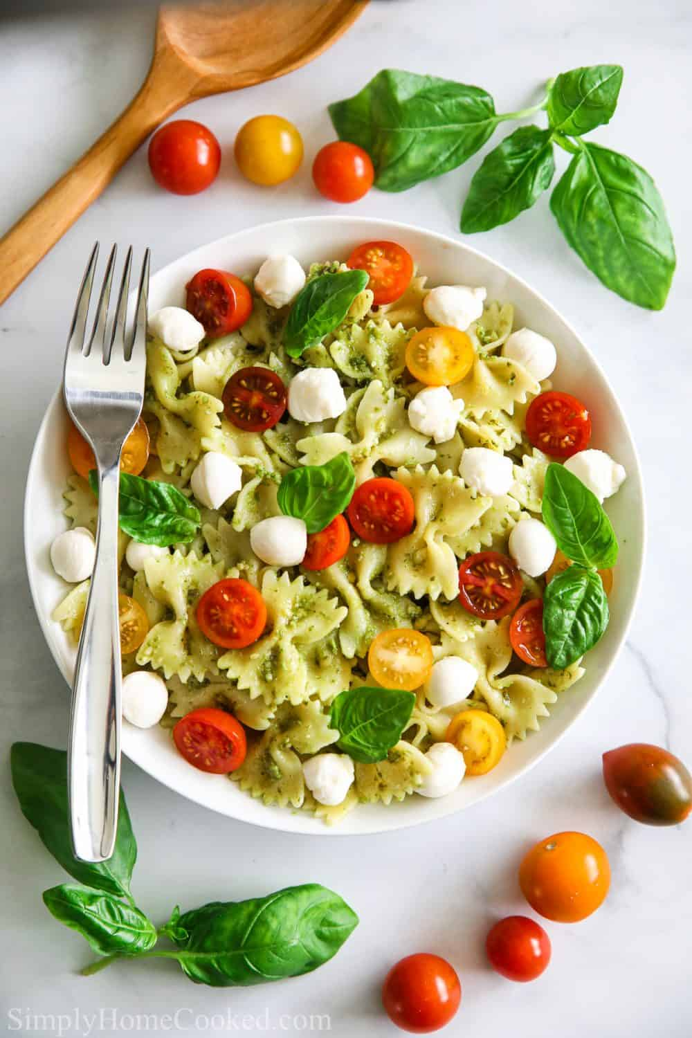 overhead shot of pesto pasta salad with basil leaves, sliced cherry tomatoes, mozzarella pearls,, and a fork laid on top