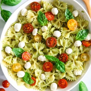 close up photo of pesto pasta salad with mozzarella pearls, basil leaves, and sliced cherry tomaotes on top