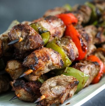 Close up photo of pork kabobs shashlik on a white narrow plate
