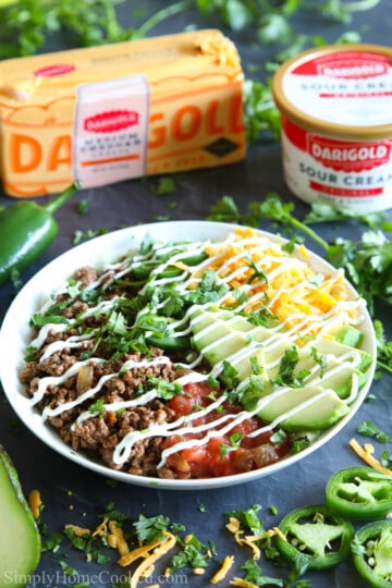 close up photo of beef taco bowl with avocado, salsa, shredded cheese, and sour cream drizzle on top