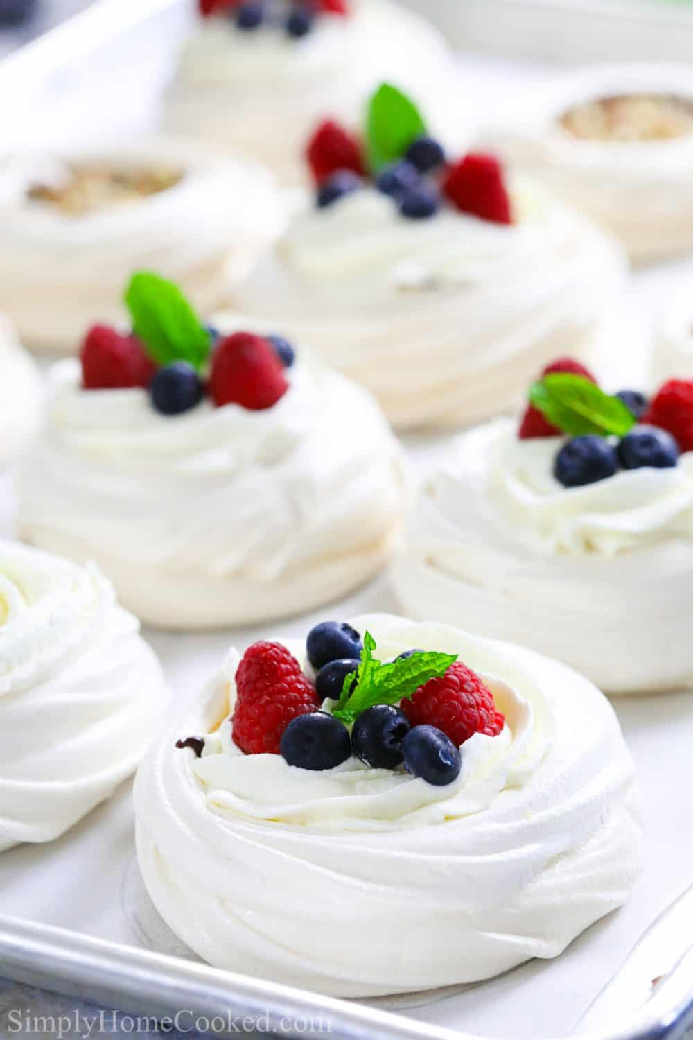 mini pavlovas with whipped cream, berries, and mint on top