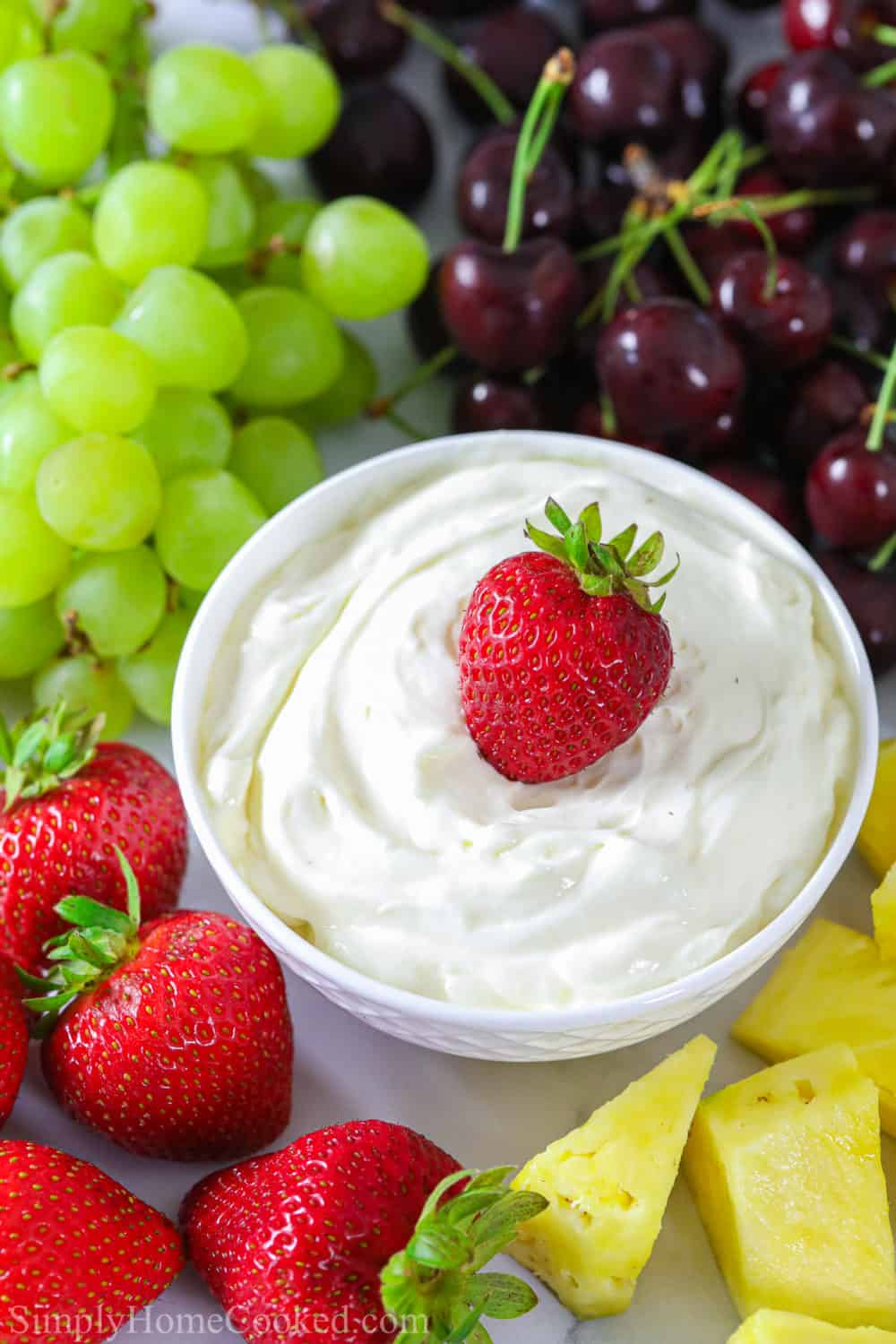 Cream cheese fruit dip in a small white bowl with a strawberry dipped into it and grapes, cherries, and pineapple beside it