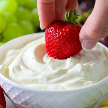 Cream cheese fruit dip in a small white bowl with a hand dipping a strawberry into it