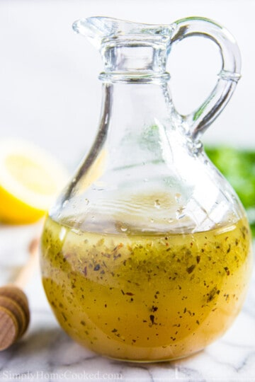 homemade greek salad dressing in a small glass pitcher