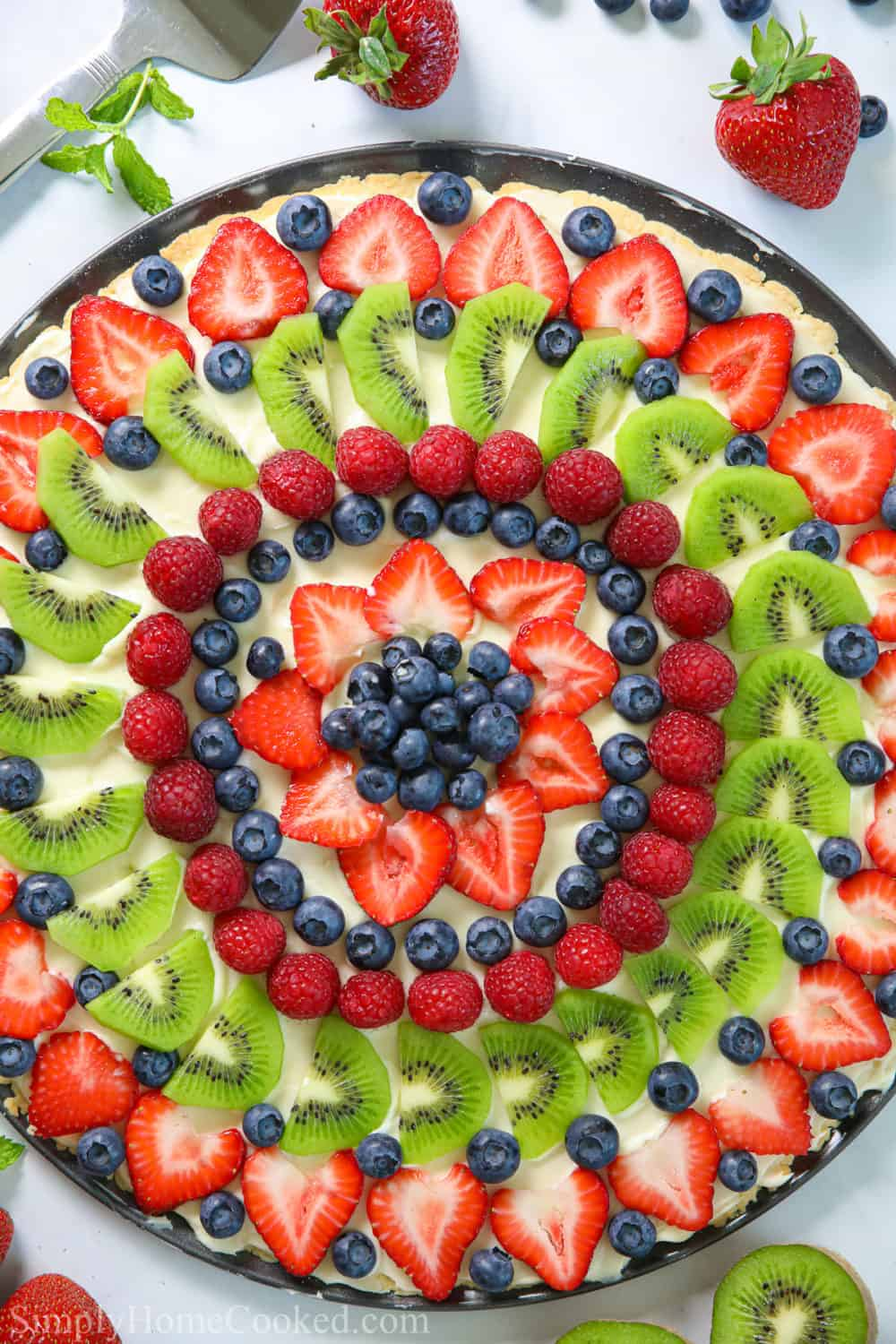 overhead shot of homemade fruit pizza with strawberries, blueberries, raspberries, and kiwi