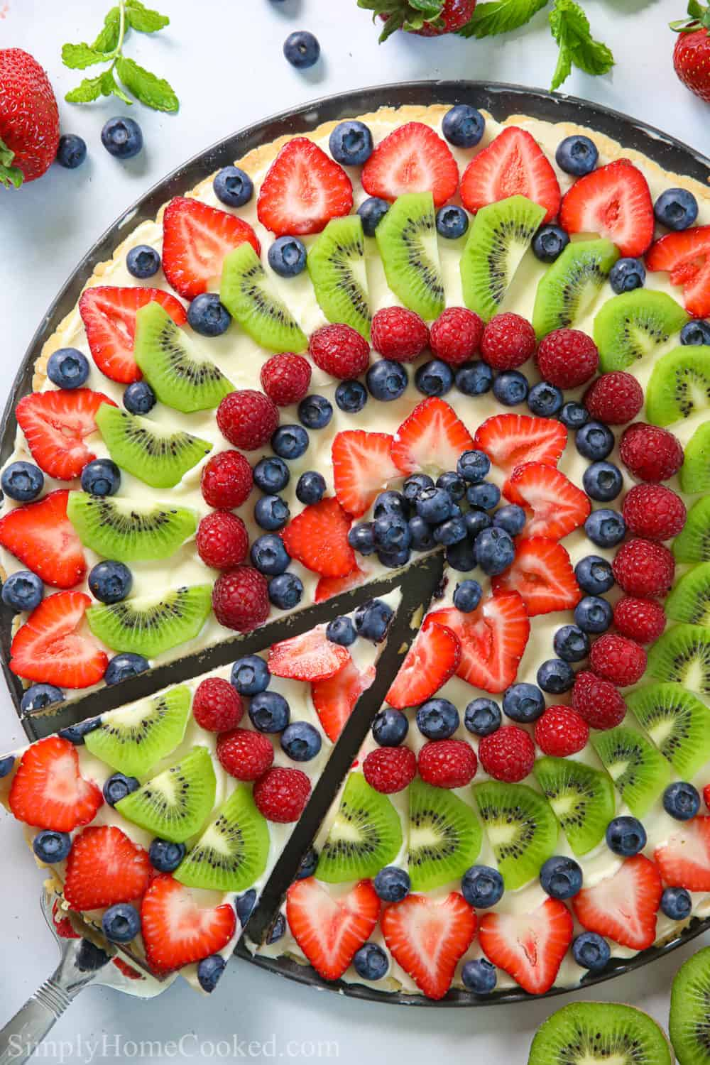 overhead picture of a fruit pizza that has been sliced.