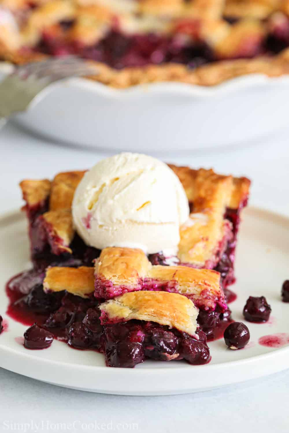 close up image of sliced homemade blueberry pie with a lattice top and vanilla ice cream on top