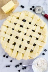 overhead image of homemade blueberry pie with a lattice pie crust on a white background