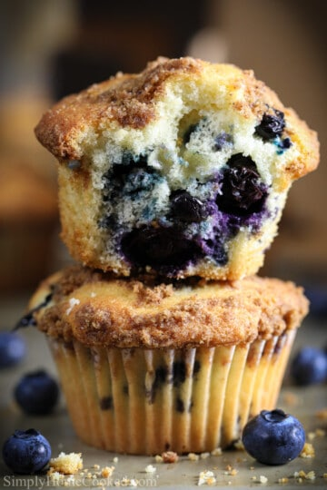 two stacked blueberry muffins, with a bitten muffin on top