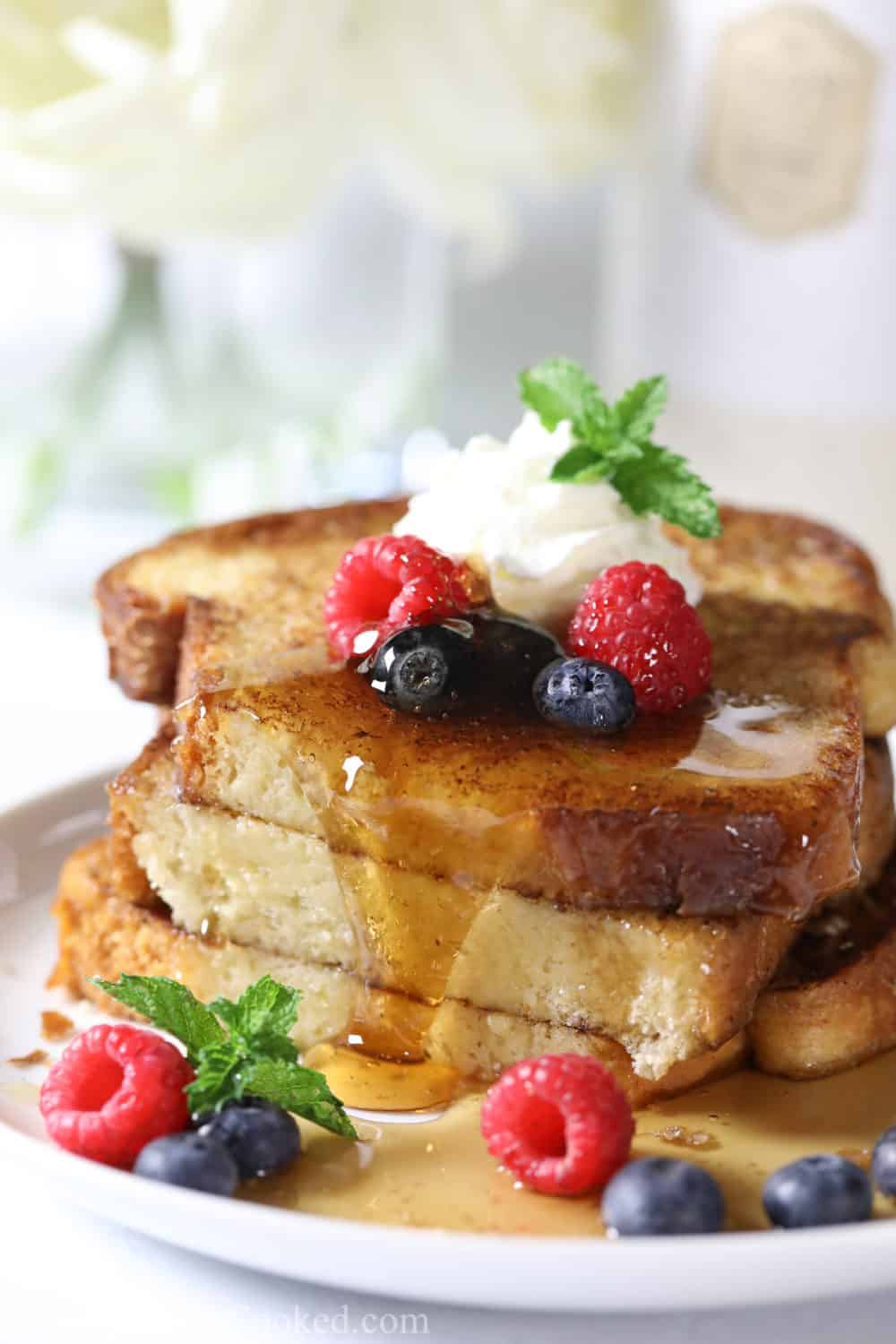 close up image of sliced brioche french toast with maple syrup, raspberries, blueberries, and mint on top