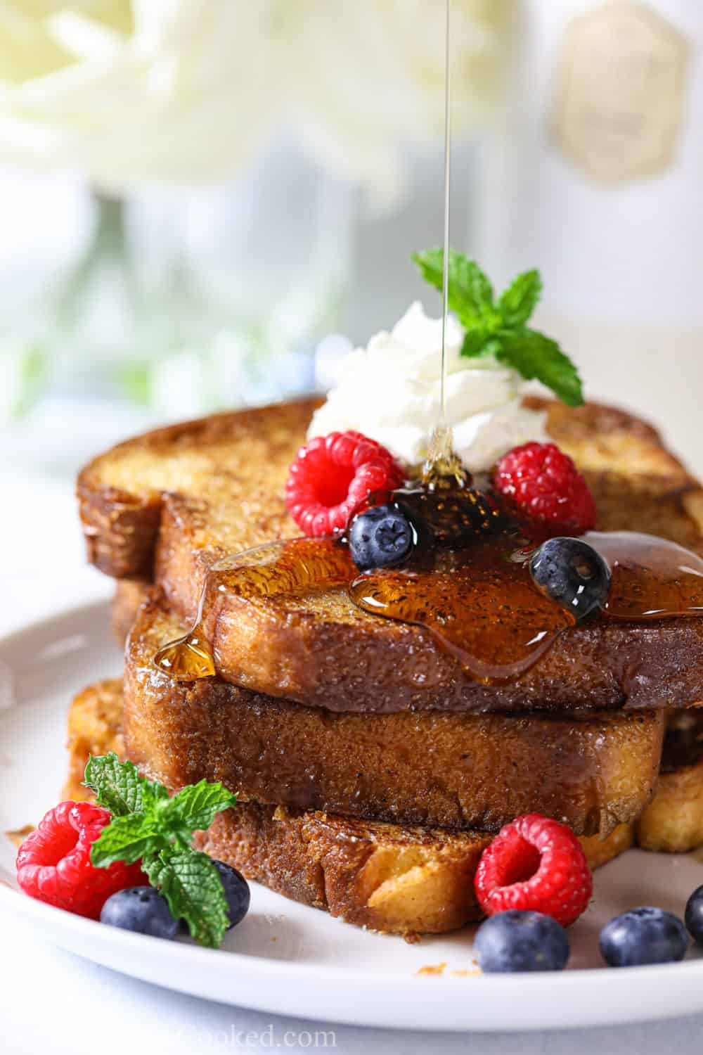 a stack of fluffy brioche french toast with berries, whipped cream and syrup on top