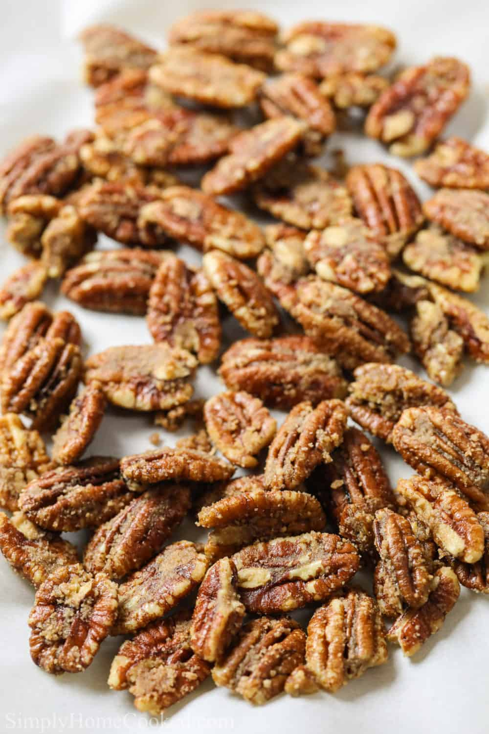 close up image of homemade candied pecans cooling on parchment paper