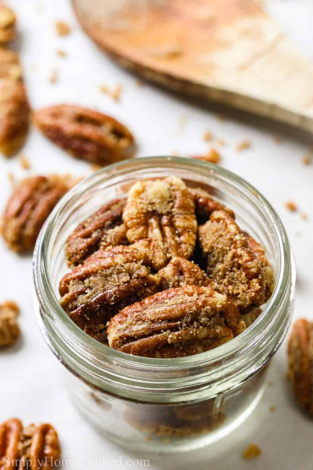 close up image of homemade candied pecans in a small mason jar