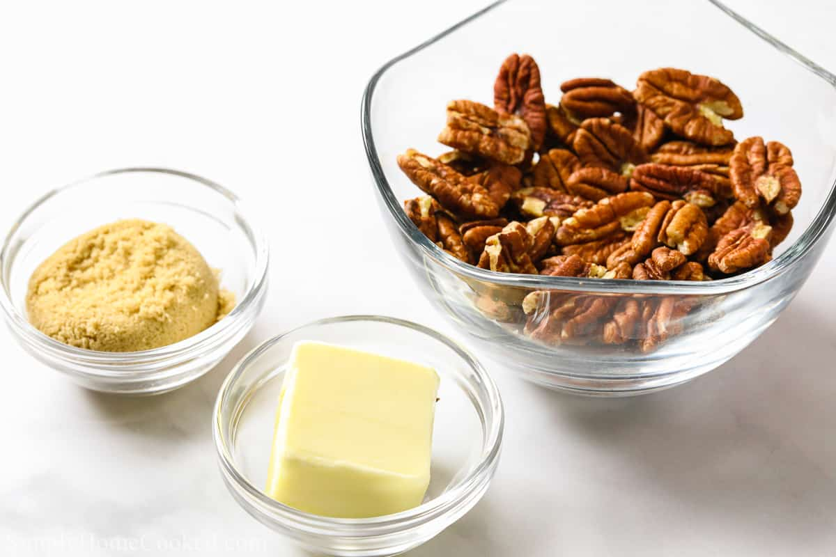 ingredients for candied pecans, butter, brown sugar, and pecans on a white background