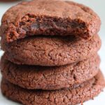 close up image of a bitten Nutella cookies stacked on top of Nutella cookies