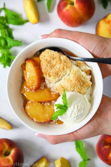 freshly baked homemade peach cobbler in a white bowl with vanilla ice cream and mint on top