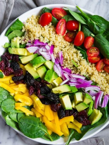 overhead shot of spinach salad in a white plate with quinoa, tomatoes, avocado, and red onion on top