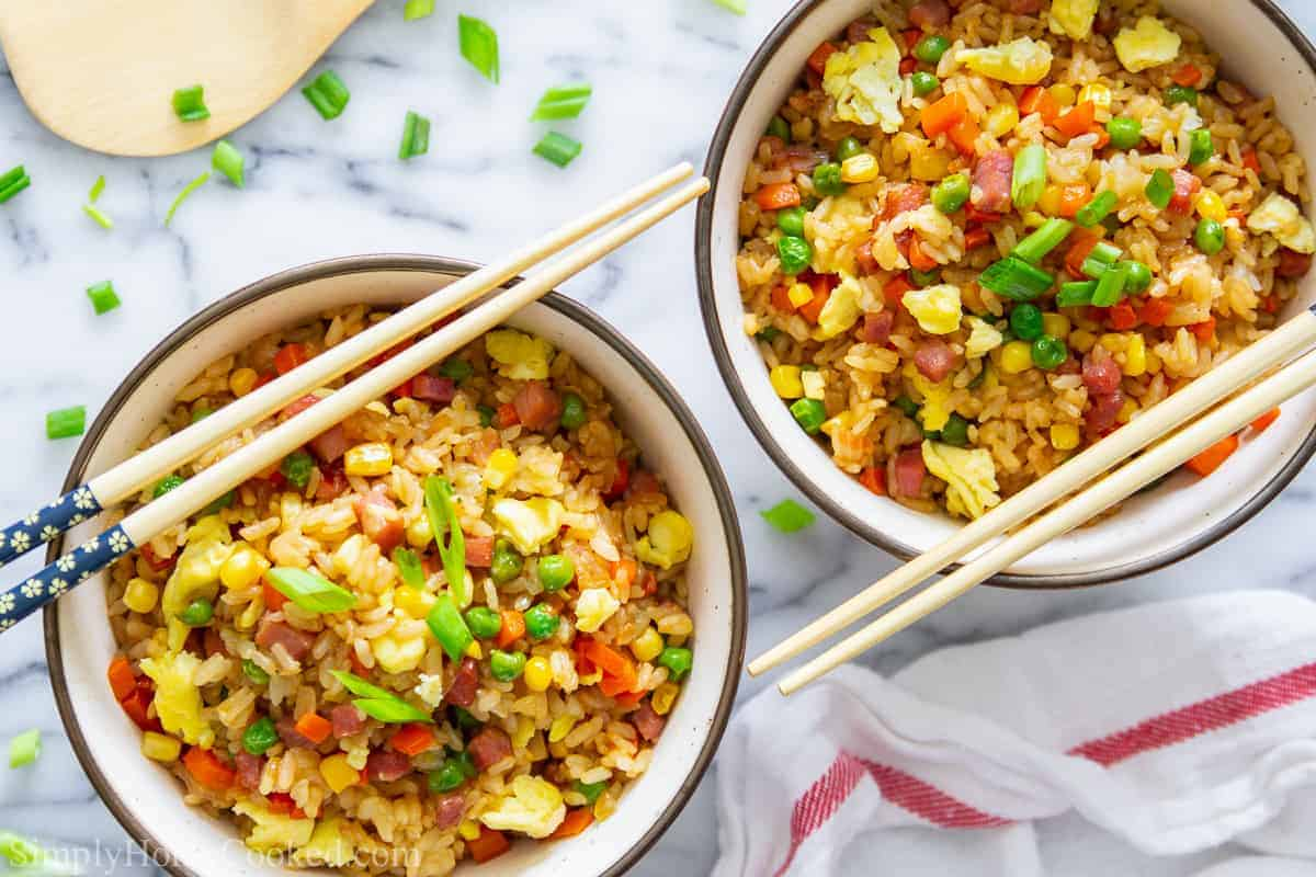 overhead image of pork fried rice in two bowls with green onion, peas, scrambled eggs, and corn on top. With chop sticks beside it.