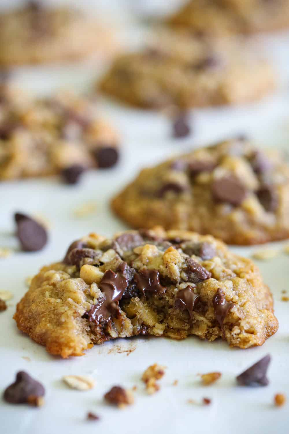 close up image of a bitten oatmeal chocolate chip cookie with walnuts and chocolate chips scattered beside it on a white background
