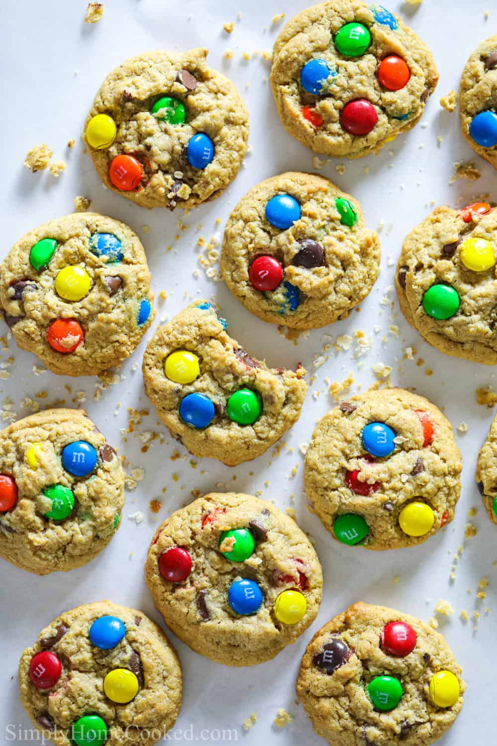 Monster cookies on a white background with crumbs and one cookie with a bite taken out of it.