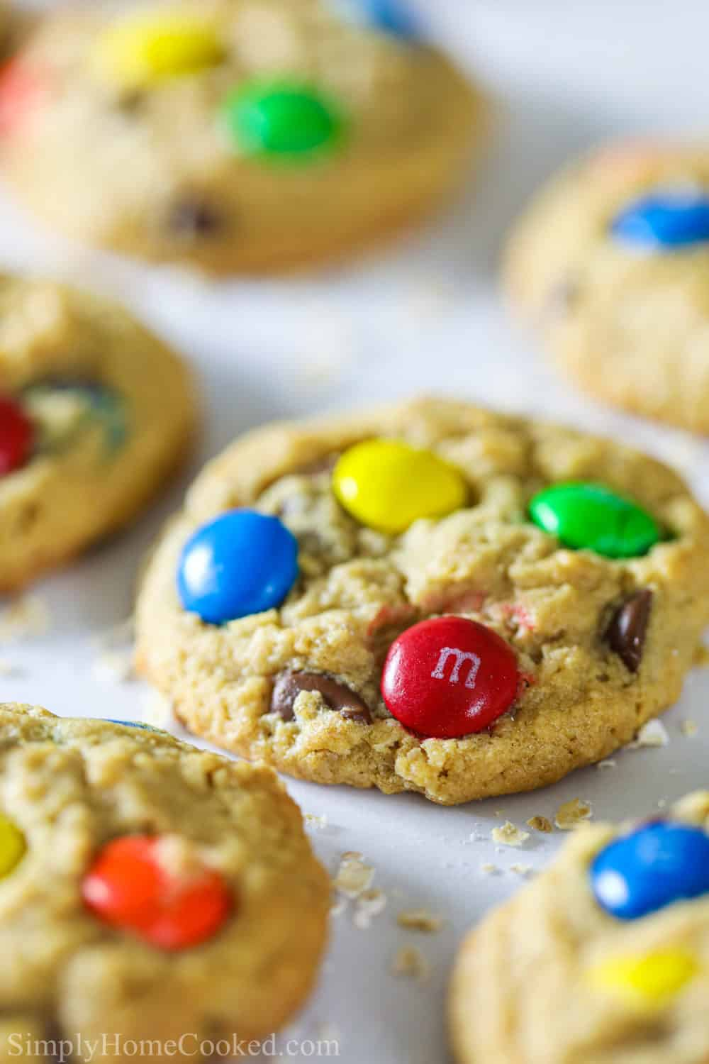 Close-up of monster cookie with M&Ms, with other monster cookies and crumbs in the background, sitting on white parchment paper.