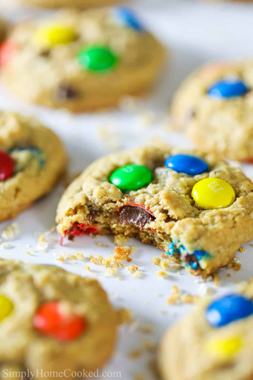 Close-up of a monster cookie with M&Ms on white parchment paper with other cookies in the background.