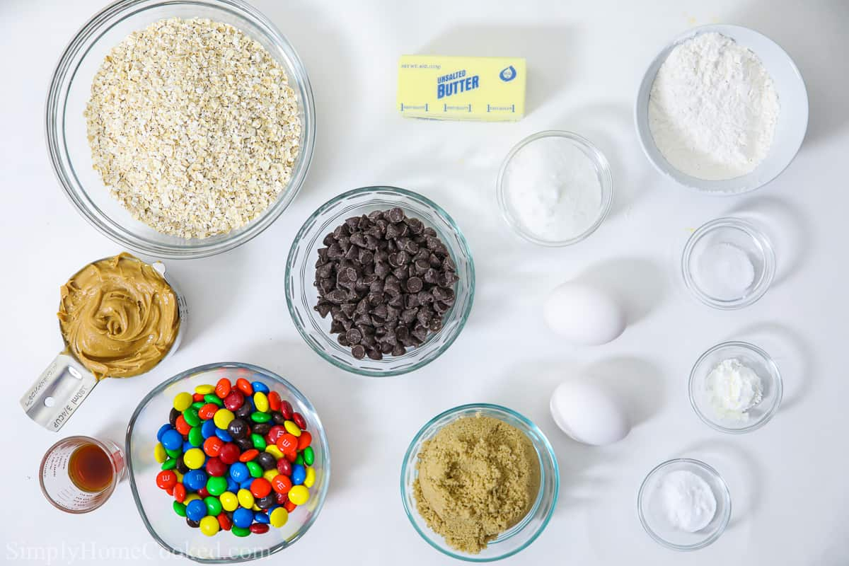 Ingredients for monster cookies: bowls of oats, flour, sugar, salt, baking soda, cornstarch, M&Ms, chocolate chips, and peanut butter, with vanilla and a stick of butter on a white background.