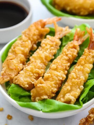 close up image of crispy fried shrimp tempura on a plate lined with butter lettuce leaves
