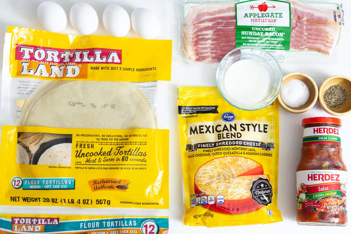 Ingredients for breakfast burritos: flour totillas, bacon slices, shredded cheese, salsa bottle, and small dishes of milk, salt, and pepper.
