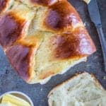 an overhead image of sliced brioche bread on a baking sheet with a butter knife and butter beside it
