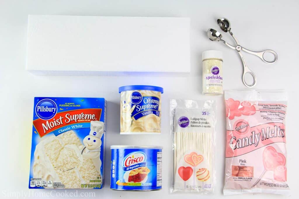 overhead image of ingredients for cake pops on a white back ground including cake mix, frosting, cake pop sticks, and candy melts